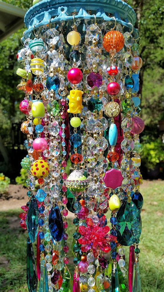 Gorgeous! And large!!  This wind chimes unique top is reminiscent of a carnival tent ~ completely decked out in dazzling rhinestones and crystals...so fun!  This antique brass top is painted Mediterranean blue and embellished with rhinestone trim in orange, clear and shades of blue. Each strand has a Tiffany~set rhinestone at its end. Crystal and glass beads are attached between each of the rhinestones, so the top is gorgeously full and sparkly!  Layers of crystal, glass, stone, ceramic…