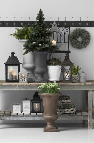 urns and lanterns with greenery on Christmas console table display