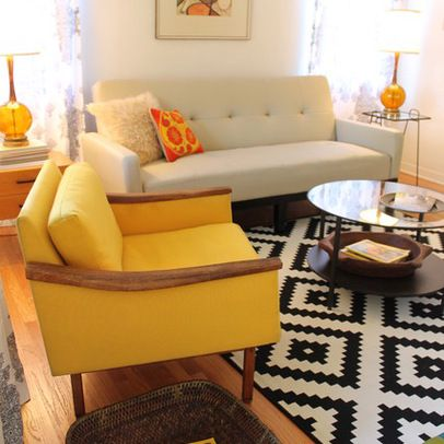 Black and white rug creates an interesting contrast to the yellow chair and accent pieces.