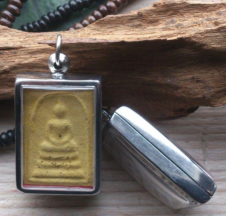 """Een bijzonder Boeddha sieraad; 'n aardewerk amulet met de afbeelding van Boeddha in een metalen """"doosje""""."""