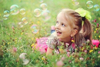 Sweet, Happy, Smiling Six Year Old Girl Laying On Grass with Bubbles Royalty Free Photo