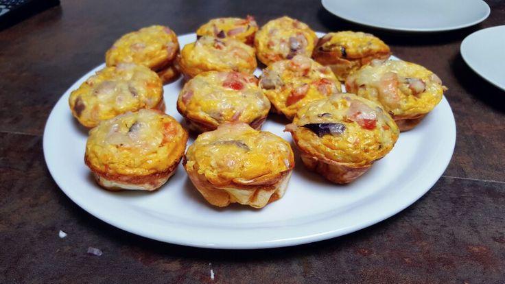 MINI OMELETTES: Préchauffer four à 110°. Pour 14 muffins, battre 14 oeufs dans un saladier et ajouter un peu de lait. Dans un plat à part, couper en morceaux 1 gros oignon, 2 carottes, un demi poivron, 1 tomate, lardons et ajouter sel poivre paprika et cumin. Ajouter le mélange aux oeufs et remuer avec cuillère. Mettre des ronds de pain pitta au fond de chaque ramequin et badigeonner de beurre. Verser le mélange et ajouter gruyère râpé au dessus. Enfourner 20min.