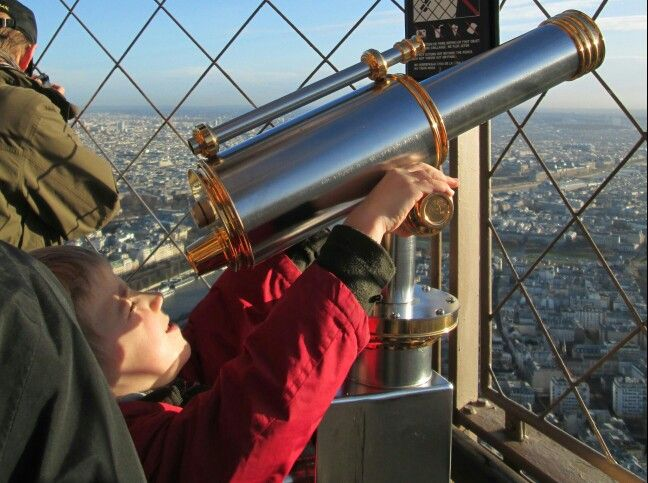 paris eiffel tower boy looking at sky through telescope on observation deck