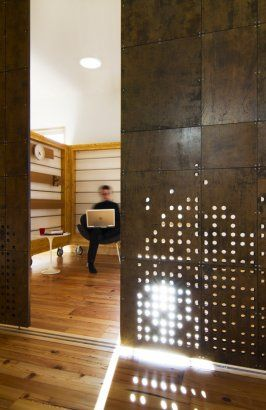 perforated metal interior partitions. Live Work House, Syracuse, United States  by: Cook + Fox Architects