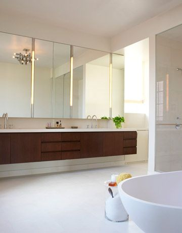 """Spa-Inspired Bathroom The master bath is """"generous with space and light."""" A wall of mirror hangs above a walnut double vanity. A floating Agape tub sits atop pale limestone floors."""