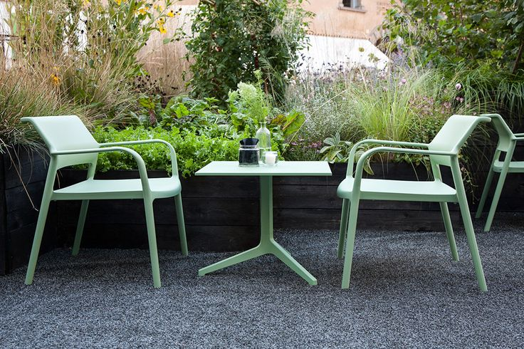"""Sage-green furniture set by Jorge Pensi: Gently rounded armrests and a curving backrest characterize the weatherproof """"Ara Lounge"""" #chair of polypropylene. Matching #table """"Ypsilon"""" with its four-star base comes across as especially light. #outtdoor"""