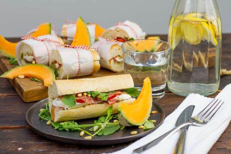 Recept voor italiaanse sandwich voor 4 personen. Met olijfolie, stokbrood, mozzarella, Parmaham, Italiaanse kruiden, cantaloupe-meloen, tomaat, groene pesto, pijnboompitten en rucola