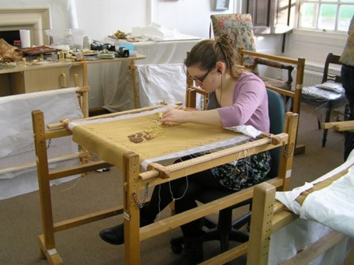 RSN Degree student Hanny Newton working one of the bodice panels on a slate frame