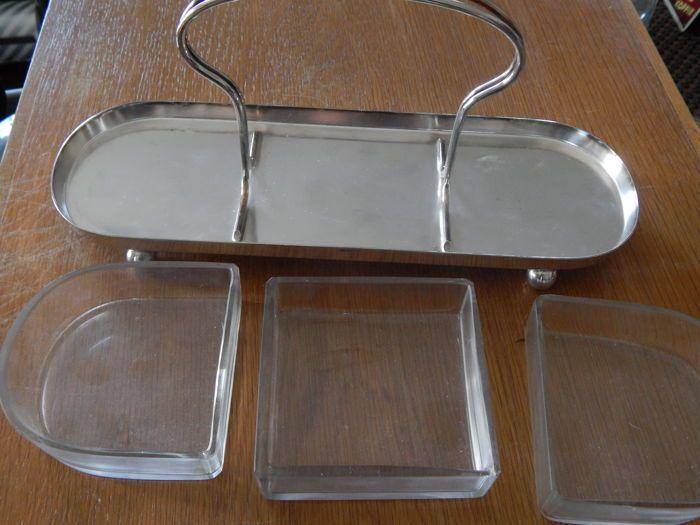 Art Deco Zilveren serveerschaal met kristalglazen inzet.  Een heel leuke art deco serveerschaal van zilver met een driedelige kristalglasinzet. De schaal is in prima staat en heeft geen beschadigingen ook de glazen inzetten zijn zonder gebreken.De afmetingen zijn 31 bij 10 cm. en 14 cm hoog.  EUR 0.00  Meer informatie