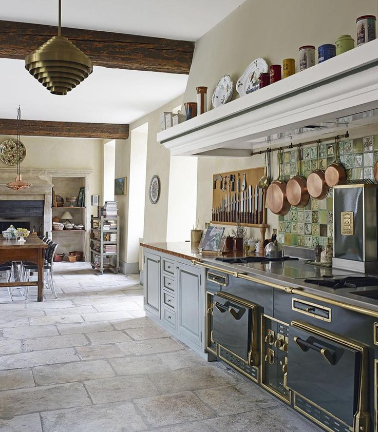 Copper pans compliment hand-painted ceramic tiles from Carreux de Chesley in this Provençal kitchen. Formerly a storeroom, the space was enlarged and a traditional fireplace and flanking shelving specially made to echo the traditional Provençal feel which pervades the former abbey   Photograph David Cleveland   Homes & Gardens