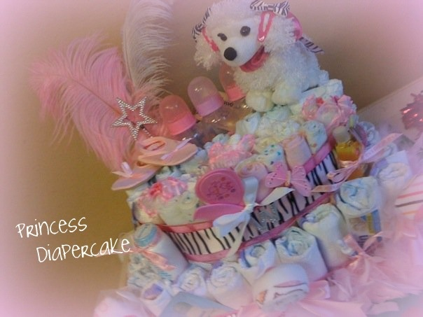 Diaper cake made with 1 package of size 1 diaper, and 1 package of newborn diapers, and a package of wash cloths rolled.  Decorated for a pretty little princess.
