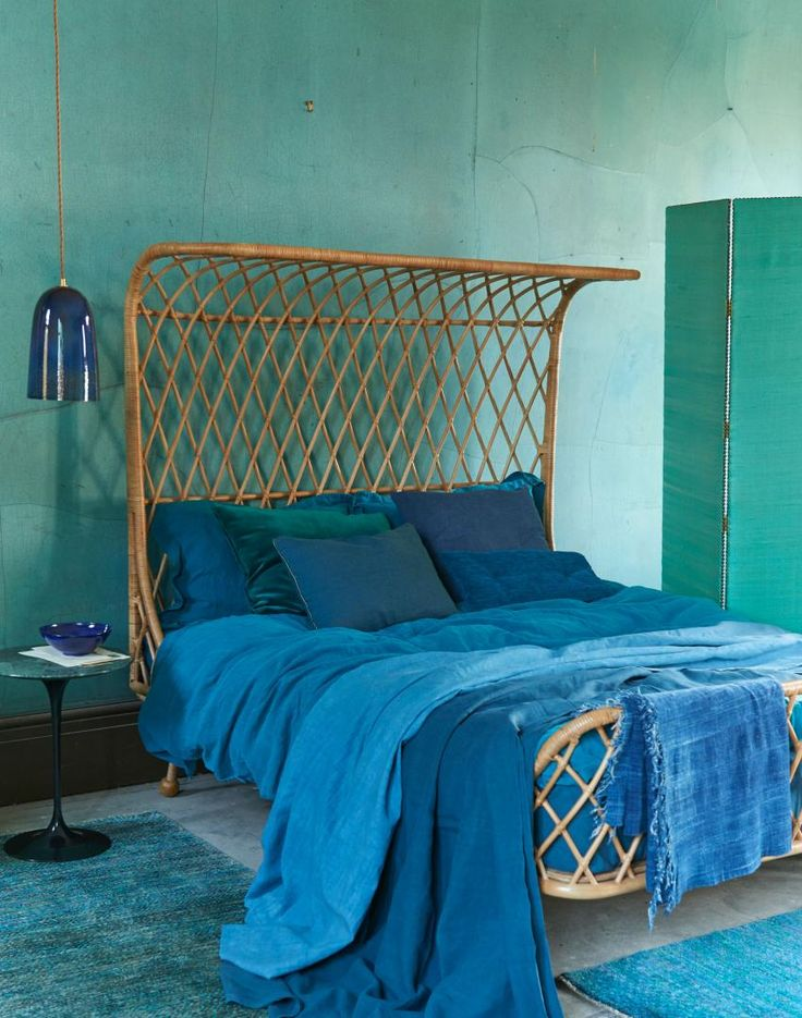 Teal Bedroom With Blue Soft Furnishings And Rattan Bed
