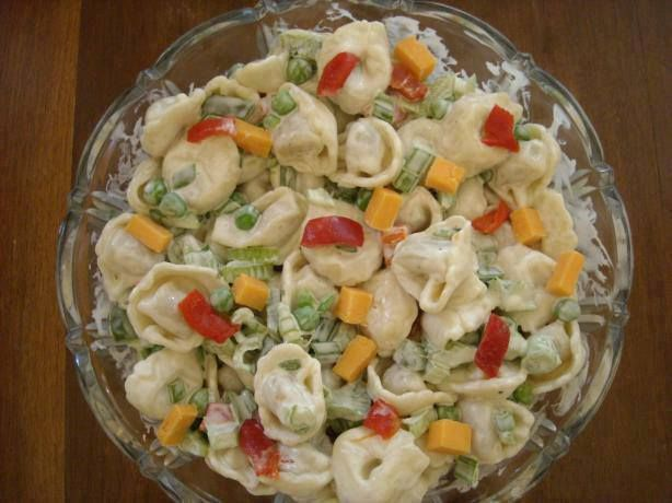 Easy Tortellini Salad   2 (19 ounce) bags frozen cheese, tortelinni 1 lb frozen baby peas 2 celery ribs, diced 3 green onions, diced 1/2 green or red peppers. Ranch dressing 1 cup cheddar cheese (opt). Directions Boil your frozen tortellini in salted water until they pop up to the surface or desired doneness. Drain pasta , rinse in cold water, allow to drain again. Add all veggies. Top with Ranch salad dressing.