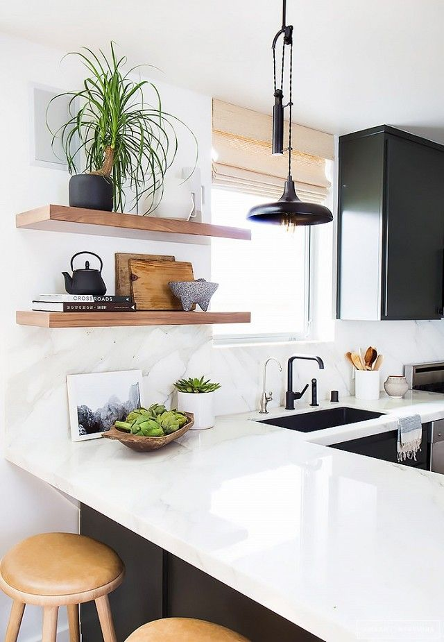 Kitchen with an industrial pendant light, white countertops, and wood shelves