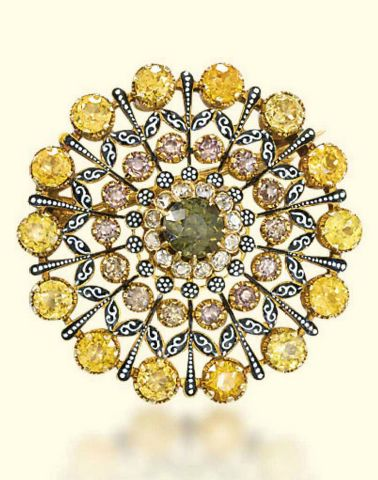 A RENAISSANCE REVIVAL ZIRCON AND ENAMEL PENDANT/BROOCH, BY CARLO GIULIANO. The openwork medallion with a central green zircon within a border of diamonds and concentric rings of yellow and brown zircons, accented with black and white piqué enamel, a folding pendant loop to the top, mounted in gold, circa 1890, with maker's initials 'C.G.' for Carlo Giuliano. #Giuliano #RenaissanceRevival #brooch #pendant