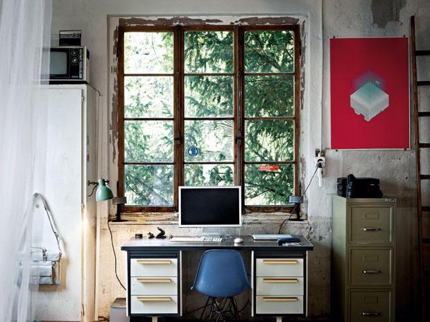 Un angolo studio della casa: una vecchia scrivania collocata in prossimità della grande finestre, dagli infissi scrostati e segnati dal tempo