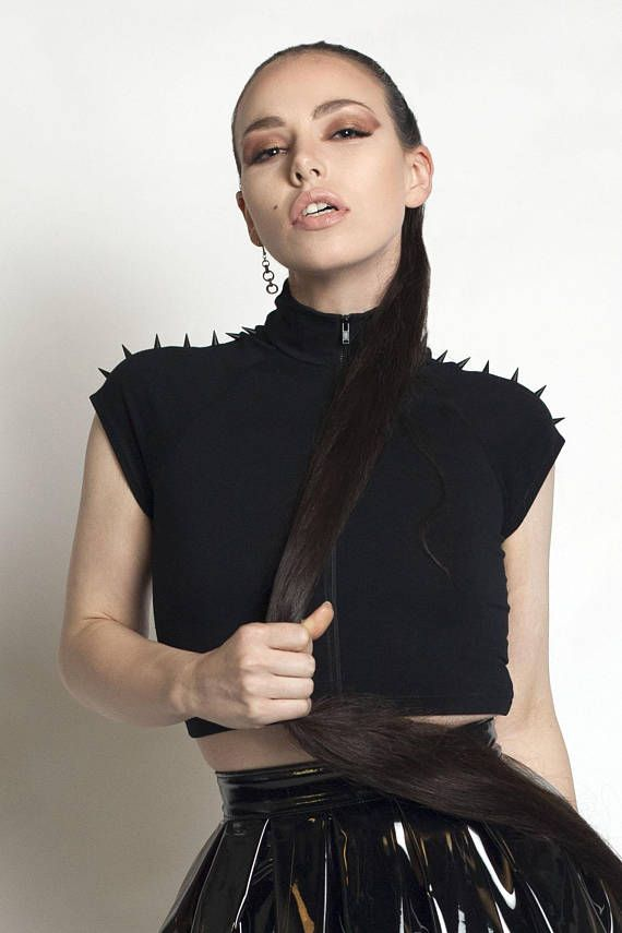Kinetic black spiked crop top with exposed black metal zipper front! This shirt features super pointy black spikes with high collar and super stretchy cotton lycra fabrication. Perfect for any deathrock, cyber, rave, ninja, cybergoth, punk or nu goth outfit!  #blackfashion #spikes #goth #croptop #deathrock #punk  #fashion #sleeveless #womensfashion #clothing #blackshirt