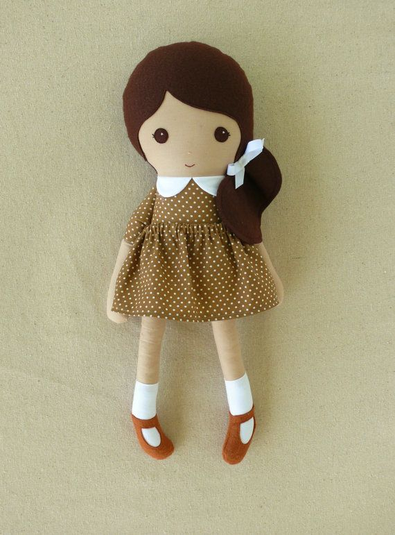 This is a handmade cloth doll measuring 18 inches. She is wearing an old-fashioned brown and white polka dotted dress with a white collar and a