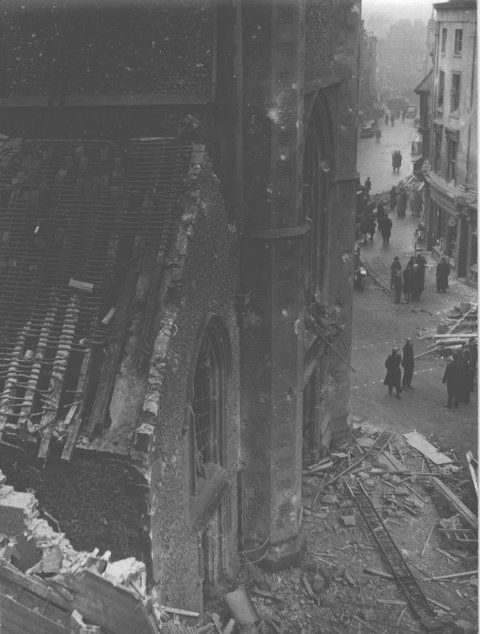 Towards the end of 1942 and the beginning of 1943, German air raids on Britain intensified. On 10 February 1943, four bombs were dropped on Reading town centre. The Town Hall on Blagrave Street was badly damaged as were businesses on Minster Street. 41 people were killed, mostly customers at the People's Pantry in Market Arcade.  This photograph was taken in the aftermath of the bombing, from Reading Town Hall roof looking south to the Market Place and St Laurence's Church.