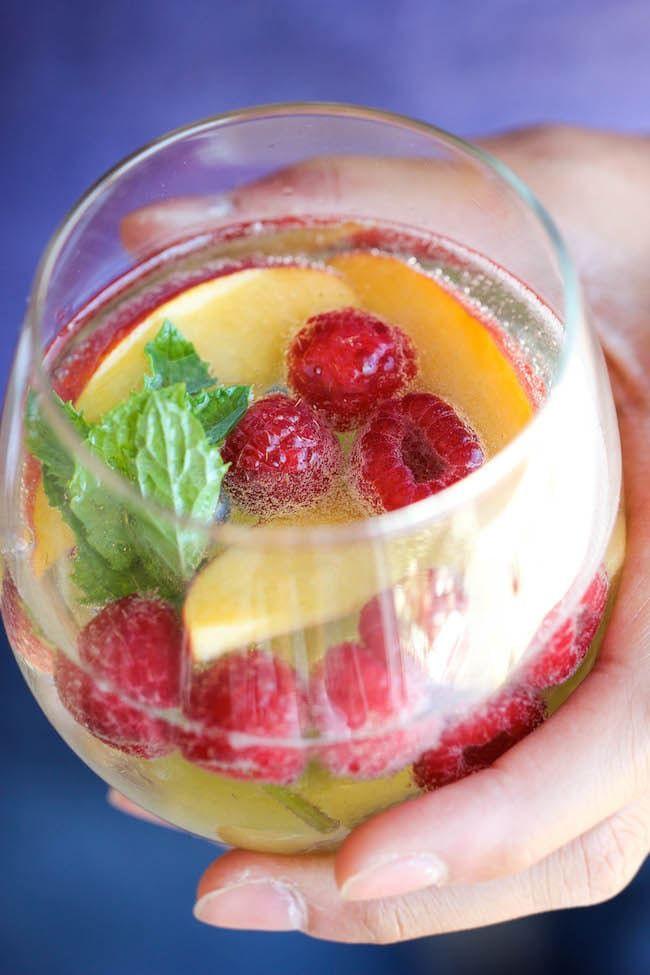 Todo lo que necesitas es: vino blanco, vino espumoso, melocotones, frambuesas, menta. Consigue la receta aquí.