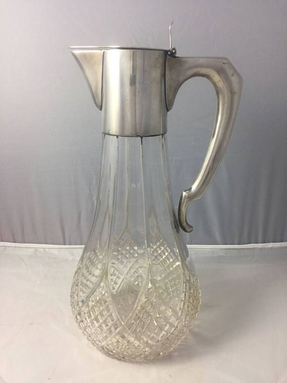 """Antique claret jug with Austro-Hungarian .800 silver mounts circa 1890 - 1900. Cut glass pitcher great for water or wine. The top of the lid has a monogram. Signed A Bachruch 41287 a hallmark in the shape of a tazza 800 then another hallmark which looks to be crescent moon shaped. The last hallmark is not clear something with a star on it possibly a crown. It measures 10 3/4"""" x about 5"""" wide. Excellent vintage condition. $25 shipping to the continental U.S.     Canada according to postal..."""