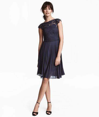 Mørk blå. En knelang kjole i vevd kvalitet med overdel i blonde. Kjolen har båtringning og holkermer. Avskåret i midjen med plissért skjørt. Skjult glidelås