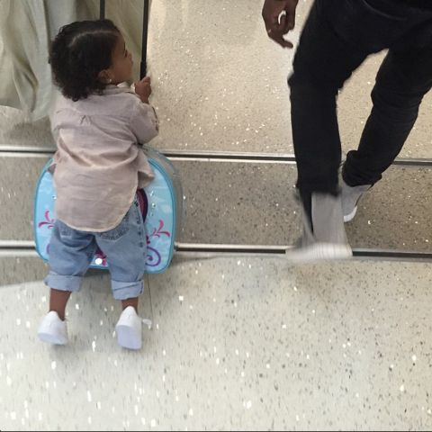 Riding her Frozen suitcase in the airport. See all of North West's best looks.