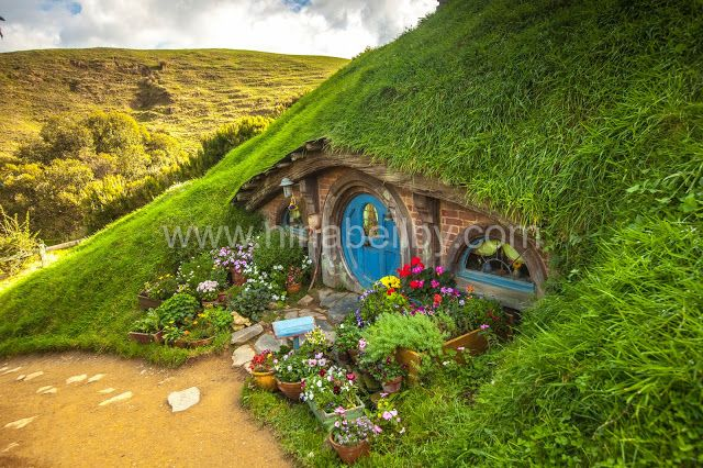 Hobbit home with blue door in the mountain at Hobbiton in New Zealand