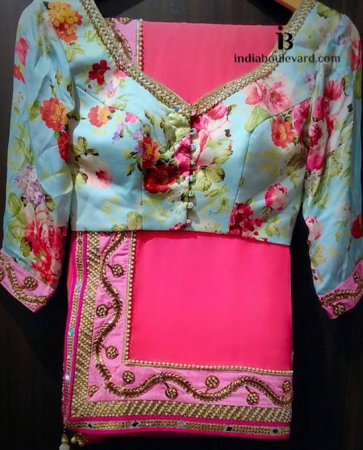 Powder blue v-neck blouse & floral prints paired with a coral pink saree. .