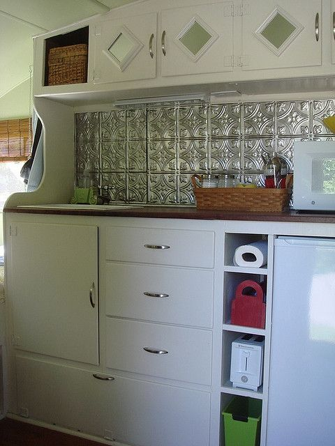 VINTAGE CAMPER RENO - custom facade on cabinetry, paint matches walls, cubbies in lower cabinets, open cabinetry on overhead with basket on display, end cap of cabinetry provides more vertical space on both sides for hanging