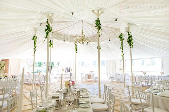 Gorgeous white lined marquee wedding with Ivory draping and chandelier.