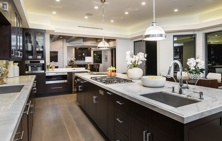 The gourmet kitchen is filled with calacatta marble countertops, Wolf appliances and a wall of Fleetwood doors that open onto a terrace for lounging with expansive ocean views. 534 Crestline Dr   Brentwood