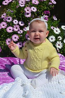 Mini Taliesin sweater baby knitting pattern. Knit in the round with beautiful cable pattern and TWO neckline options and buttons on shoulders