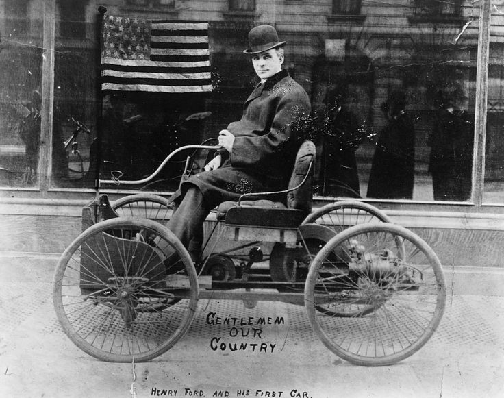 Henry Ford poses on the first car he built, the Ford Quadricycle, 1896