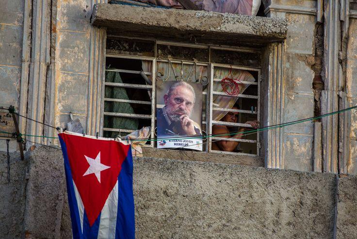 Uma foto de Fidel Castro e uma bandeira de Cuba decoram a janela de uma casa em Havana no segundo dia após a morte do ex-presidente do país