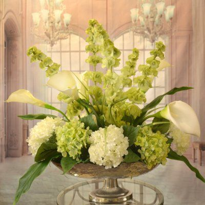 White Calla Lilly and Bells of Ireland Silk Floral Centerpiece in Silver Bowl AR349 - Clean, crisp white silk calla lilies, Bells of Ireland, white and green silk hydrangeas arranged in a hammered, silver-toned metal pedestal vase. Our silk design provides an elegant centerpiece for dining room or coffee table decor. May be customized in various sizes to fit your needs. Measures 24 H x 24 W x 14  D