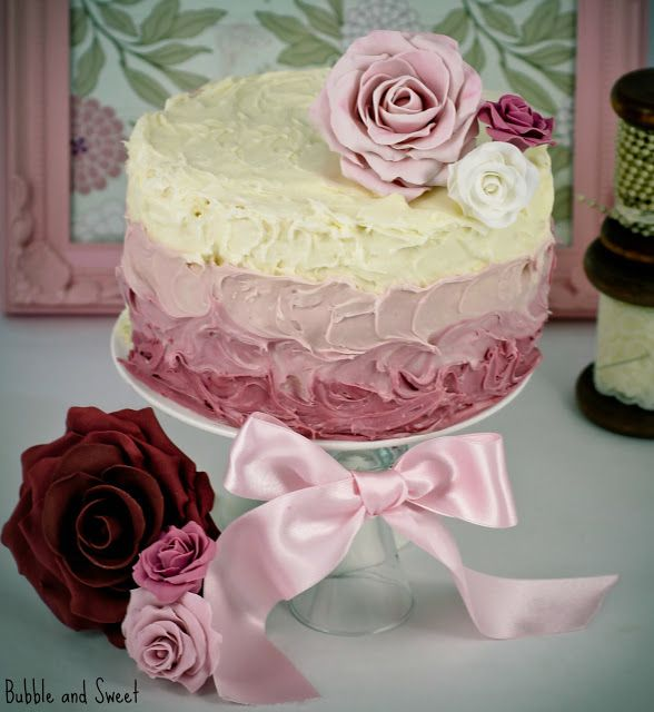 shabby shades of pink decorated with a butter knife, a tub of ready made frosting food colour and flowers.
