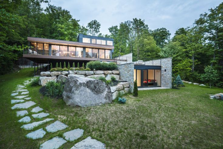 Wood And Stone Cover The Exterior Of This Multi-Level Modern House In The Forest