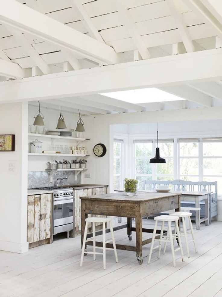 Speaking of white, this truly rustic, cottage chic kitchen balances the use of white with rough, raw woods and metal accents. The galvanized steel backsplash is a particularly nice touch. Distressed cupboard doors, antique bench, farm table, and the work bench-turned-kitchen island are great examples of how to bring old and new together without an entire kitchen remodel.