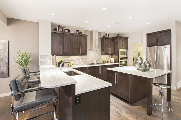 Bright marble countertops stand out against dark cabinets in the kitchen of Jayman MasterBUILTs<br></a>Allure showhome in Secord, Edmonton. Chrome fixtures and decorations complete the space<br/>and tie into the high gloss tile backsplash.