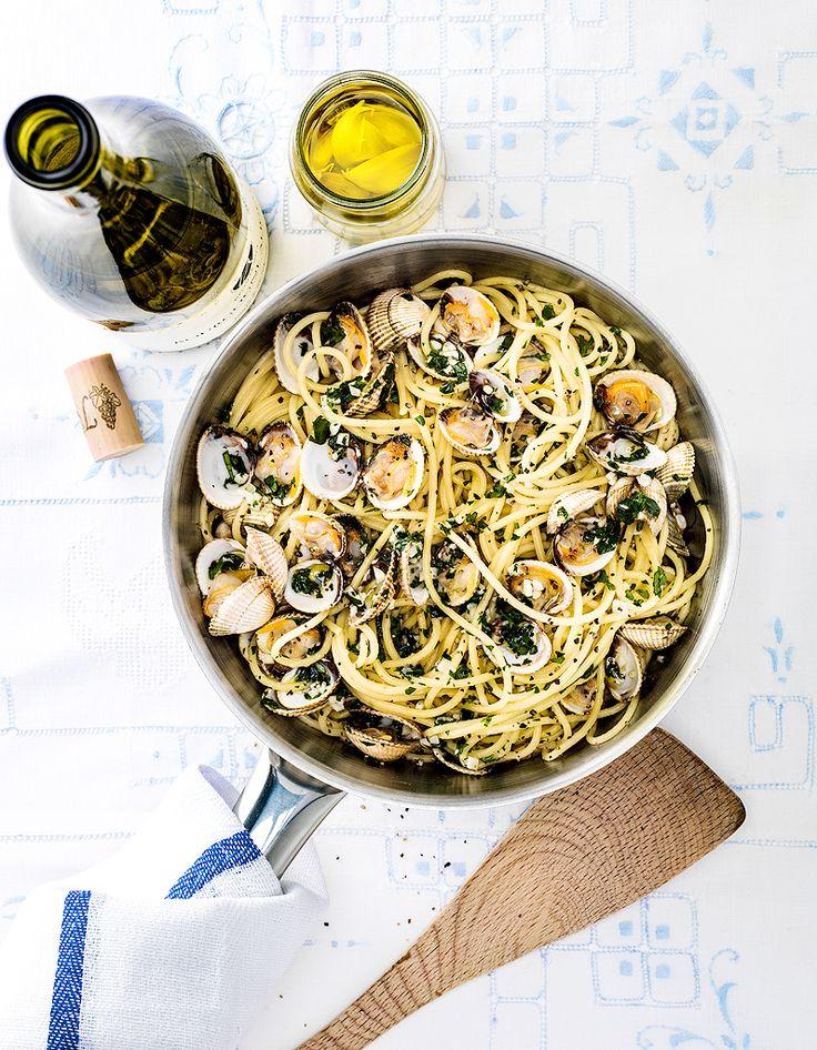 Recette Spaghettis aux coques à l'ail : Rincez les coques à l'eau courante. Faites-les cuire sur feu vif dans une grande casserole jusqu'à ce qu'elles s'ouvrent, puis versez-les dans une passoire au-dessus d'un saladier. Eliminez les coquillages fermés et réservez les autres dans la c...