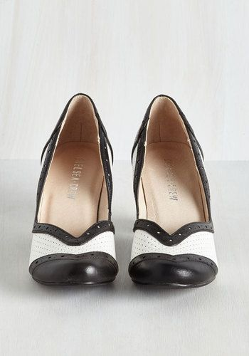 Flaunt your love of retro style by stepping in front of the camera in these black and white heels by Chelsea Crew. A modern take on a silver-screen classic, these perforated pumps showcase black trimming, leather lining, and an elegantly curved design with V-shaped toe, putting timeless fashion in action!