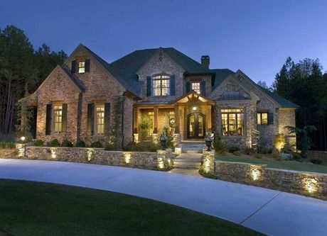 exterior lights accent the stone wall and entry of this inviting