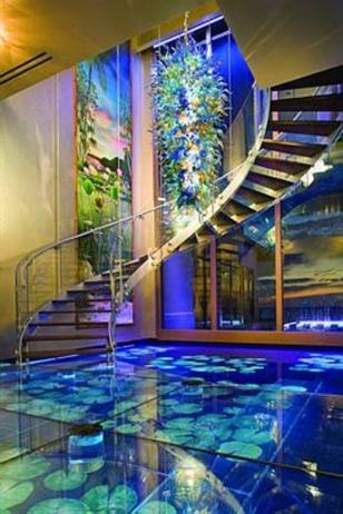 """Aquatic Abode:  Located in South Florida. A glass """"water floor"""" with hand-painted tiles, an arched aquarium wet bar and multiple indoor """"water walls"""" make this home feel like one with the water."""