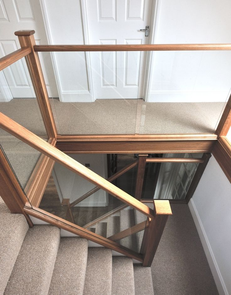 A beautiful staircase made out of glass and modern wood.