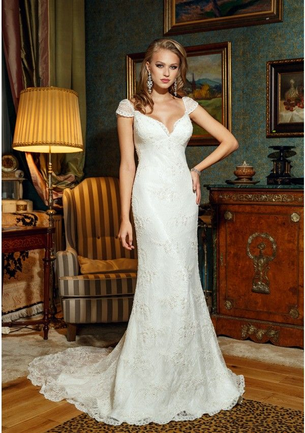 Ivory wedding gown made of lace and  manual crystals application Sensuality expressed through deep neckline and backless included bra cups A-line silhouette Short sleeve lace Long train