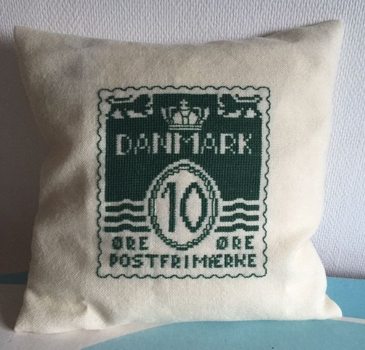 cross stitch pillow of an old Danish stamp