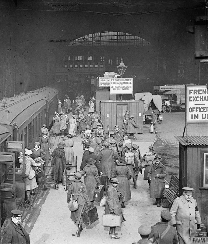 """A general view of a busy scene at Victoria Station, London following the arrival of the leave train. Crowds of soldiers and women can be seen on the platform. Several large signs read: """"French money exchanged here for officers and soldiers in uniform""""."""