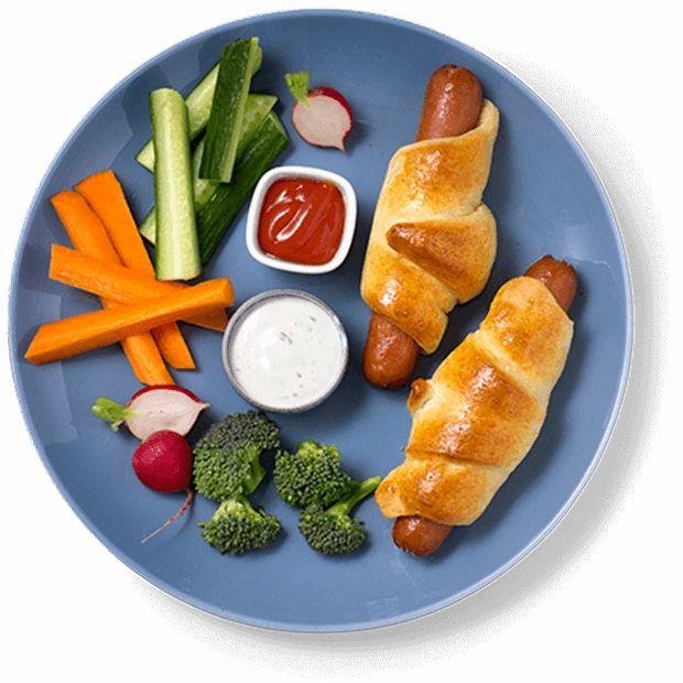 Innbakte pølser er enkel festmat for barn eller en morsom helgesnack. Serverer du rå grønnsaker til får du sunnere innbakte pølser.