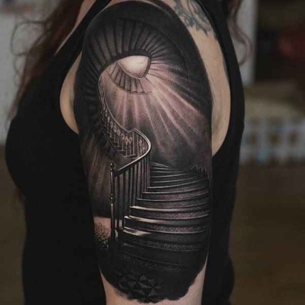 Tattoo of a staircase leading up to what seems as a tower. The light beams coming up from the windows give the tattoo that sinister yet mysterious effect.
